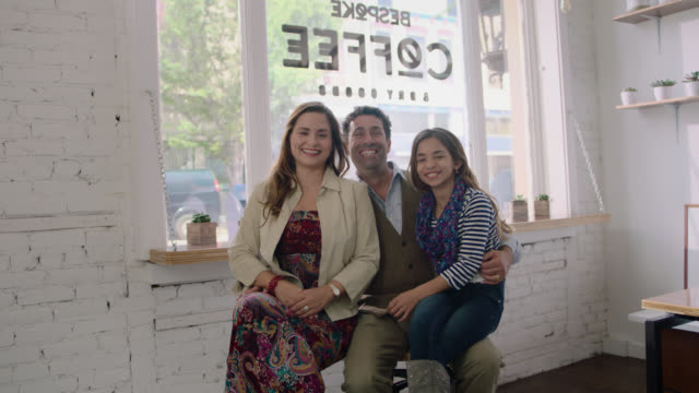 ws slo mo. portrait of family smiling at camera in locally owned neighborhood coffee shop. - logo stock videos and b-roll footage