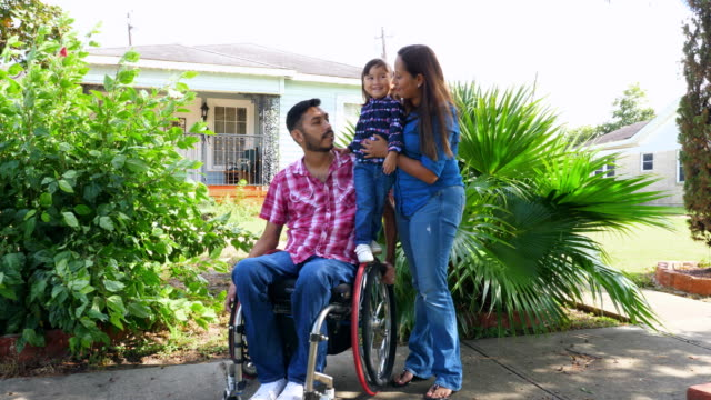 ms portrait of family with father in wheelchair in front of home - disability stock videos & royalty-free footage