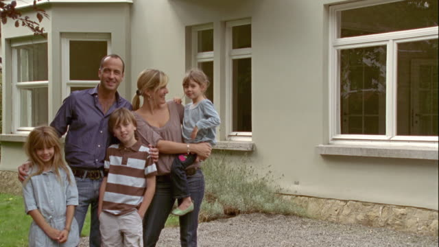 vidéos et rushes de zi, ms, portrait of family with three children (4-5, 8-9) in front of new house, brussels, belgium - devant