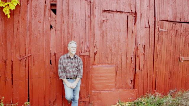 ws portrait of farmer against barn / warwick, new york,united states - auf einem bein stock-videos und b-roll-filmmaterial
