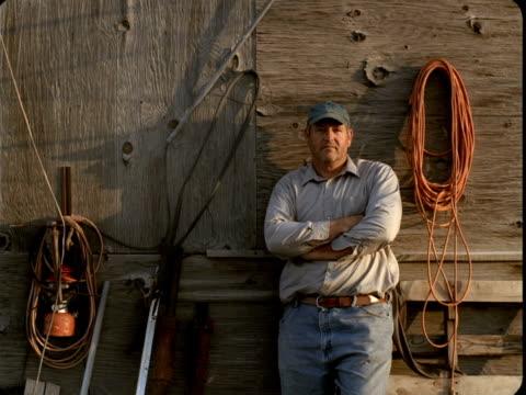 MS, Portrait of farmer leaning against wooden barn, Tonopah, Nevada, USA