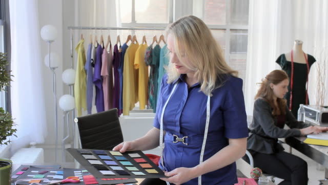 MS Portrait of fashion designer in her studio looking at color swatches / New York City, New York, USA
