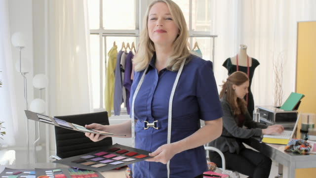 vídeos de stock e filmes b-roll de ms portrait of fashion designer in her studio looking at color swatches / new york city, new york, usa - estilista de moda designer profissional