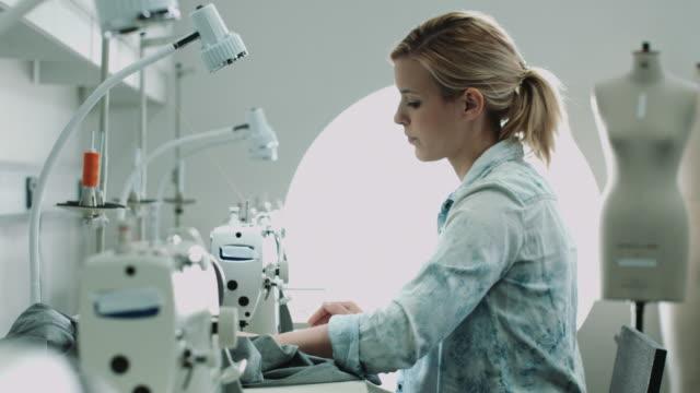 portrait of fashion designer working on sewing machine - トルソー点の映像素材/bロール