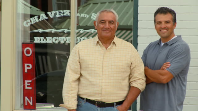 ms, pan, portrait of father and adult son small business owners standing in front of shop, richmond, virginia, usa - two generation family stock videos & royalty-free footage