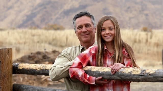 Portrait of father and daughter leaning on fence at ranch