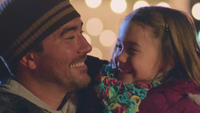 CU. Portrait of father and daughter looking at one another and smiling at camera under twinkling Christmas lights.