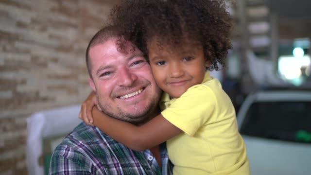 vídeos de stock, filmes e b-roll de retrato de pai e filho em casa - abraçar