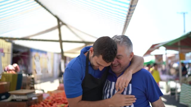 portrait of father and son hugging while working in a street market - arm around stock videos & royalty-free footage