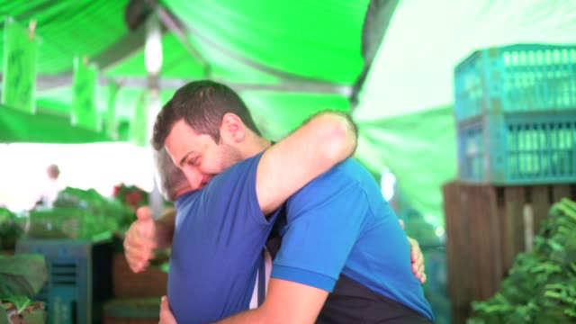 portrait of father and son hugging while working in a street market - colleague hug stock videos & royalty-free footage