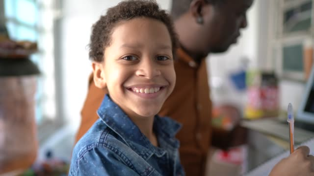 vídeos de stock, filmes e b-roll de retrato de pai e filho estudando com laptop em casa - teaching