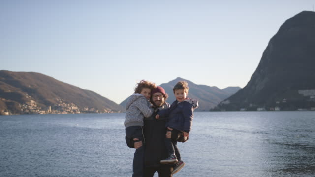 portrait of father and two children smiling by a lake at sunset - famiglia con due figli video stock e b–roll