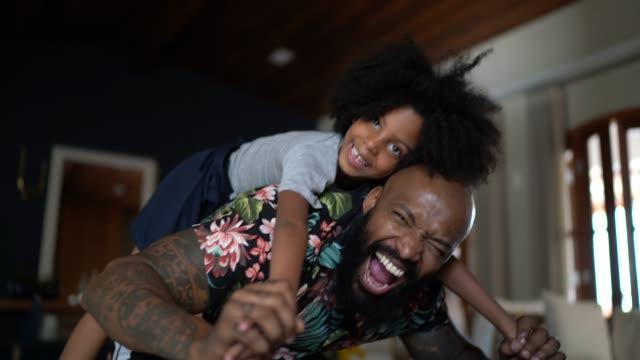 娘にピギーバックを与える父親の肖像画 - おんぶ点の映像素材/bロール