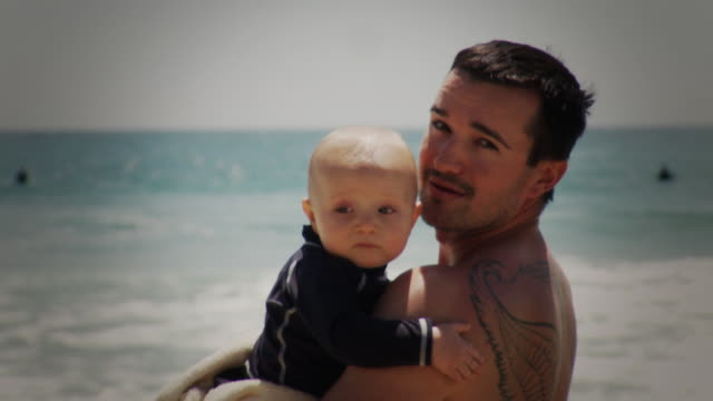 ms portrait of father holding baby son ( 6-11 months) standing on beach, laguna beach, california, usa - 6 11 months stock videos and b-roll footage