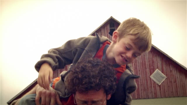 Portrait of father holding son in front of barn / lifting son onto shoulders