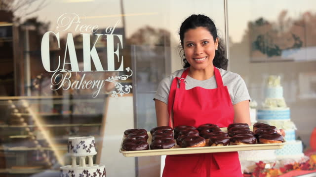 MS Portrait of female baker holding tray of donuts outside bakery / Richmond, Virginia, USA