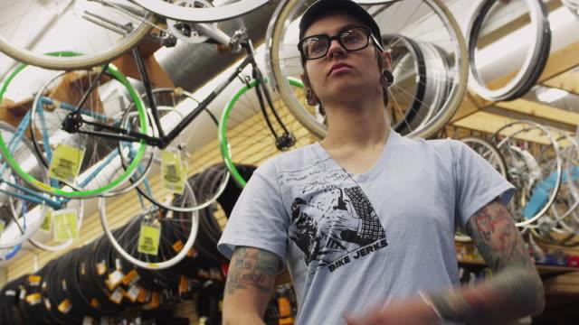stockvideo's en b-roll-footage met ms la portrait of female bike shop employee / portland, oregon, usa - armen over elkaar