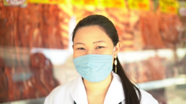 vídeos de stock, filmes e b-roll de retrato de açougue trabalhando em açougue - com máscara facial - trabalho comercial