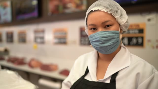 portrait of female butcher working at butcher's shop - with face mask - prevention stock videos & royalty-free footage