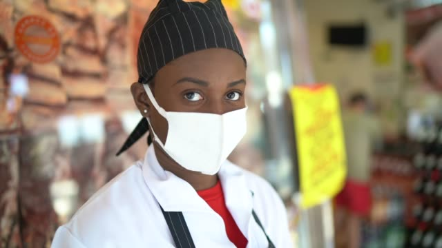 portrait of female butcher working at butcher's shop - with face mask - working stock videos & royalty-free footage