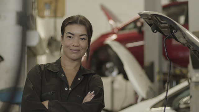 portrait of female car mechanic looking at camera in automotive vehicle workshop - manufacturing occupation stock videos & royalty-free footage