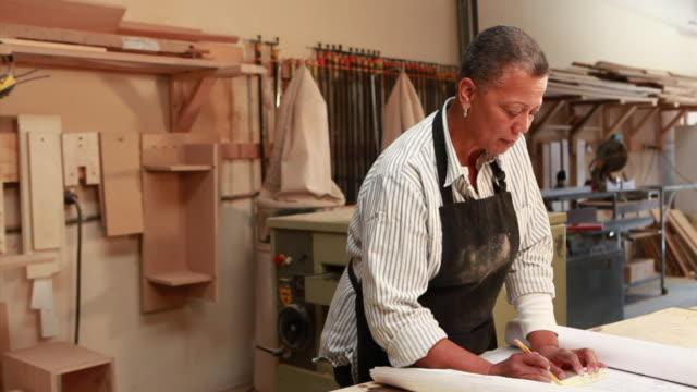 vídeos de stock e filmes b-roll de ms portrait of female carpenter working in her workshop / santa fe, new mexico, usa - só uma mulher idosa