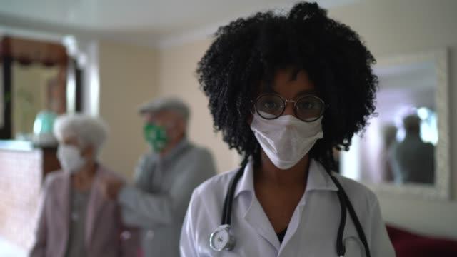 vídeos y material grabado en eventos de stock de retrato de una doctora y una pareja de ancianos en el fondo durante la visita a casa - enfermera