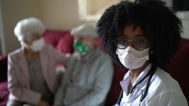 portrait of female doctor and a senior couple on background during home visit - female doctor stock videos & royalty-free footage