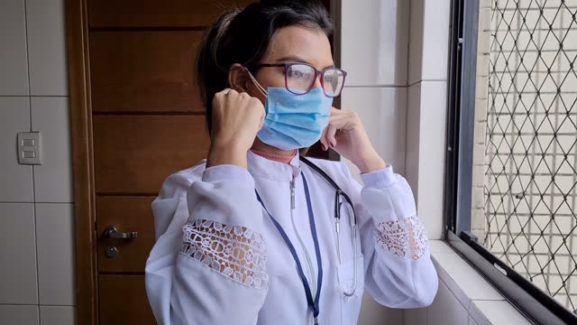 portrait of female doctor removing double protective face mask - pardo brazilian stock videos & royalty-free footage
