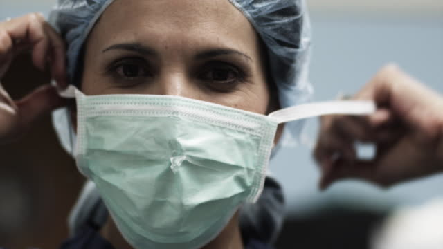 CU Portrait of female doctor removing surgical mask / Payson, Utah, USA