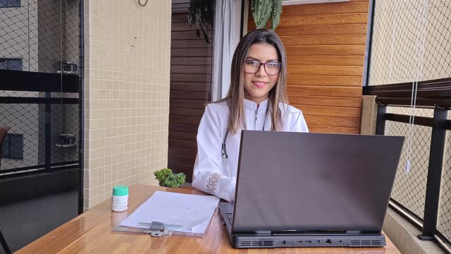 portrait of female doctor taking notes during an online appointment from home - pardo brazilian stock videos & royalty-free footage