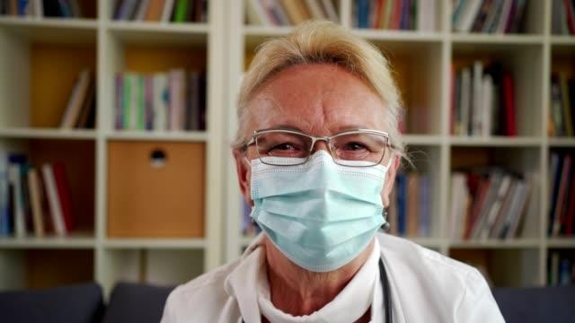 vídeos y material grabado en eventos de stock de retrato de una doctora que lleva máscara protectora - bata de laboratorio