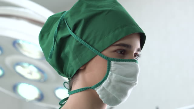 portrait of female doctor wears a surgical gown in the operating room (face) - operating gown stock videos & royalty-free footage