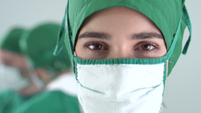 portrait of female doctor wears a surgical gown in the operating room (close-up) - operating gown stock videos & royalty-free footage