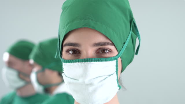 portrait of female doctor wears a surgical gown in the operating room (face close-up) - operating gown stock videos & royalty-free footage
