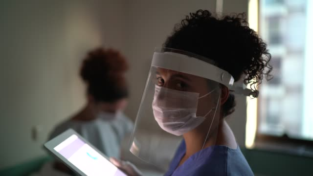 portrait of female doctor with face mask at hospital room - afro stock videos & royalty-free footage