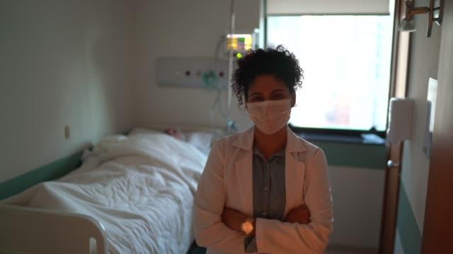 vídeos de stock, filmes e b-roll de retrato de médica com máscara facial em quarto de hospital - braços cruzados