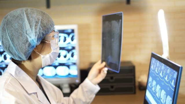 マスクとゴーグルを持つ女性医師の肖像画は、x線画像を見て、中国。 - china east asia点の映像素材/bロール