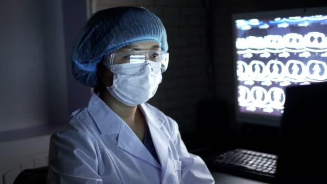 stockvideo's en b-roll-footage met portret van vrouwelijke arts met masker en beschermende brillen die röntgenbeeld ,china kijken. - medische röntgenfoto
