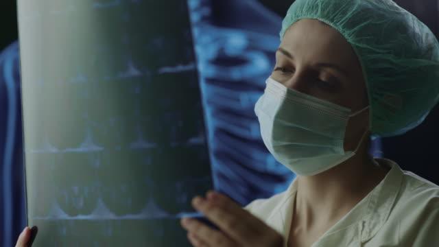 x線画像を見ている実験室でマスクを持つ女性医師の肖像画 - レントゲン点の映像素材/bロール