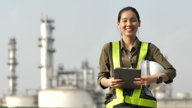 portrait of female engineer smiling to camera at industrial plant - oil industry stock videos & royalty-free footage