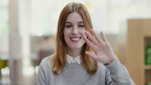 vídeos y material grabado en eventos de stock de portrait of female entrepreneur waving to camera in a modern shared workplace - saludar con la mano