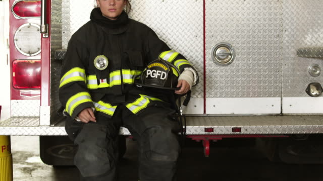 MS TU Portrait of female firefighters sitting at back of fire engine in garage, Pleasant Grove, Utah, USA