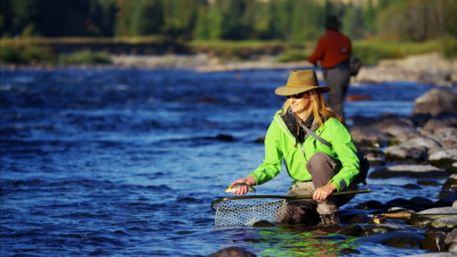 stockvideo's en b-roll-footage met portrait of female fishing after catching cutthroat trout - hengel uitwerpen