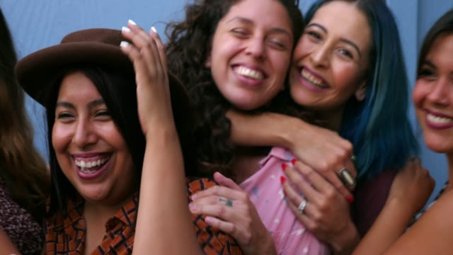 vídeos de stock e filmes b-roll de ms portrait of female friends embracing in front of blue wall - latino americano