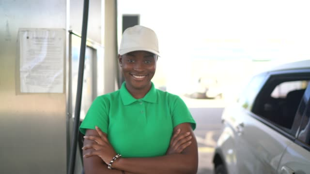 vídeos de stock e filmes b-roll de portrait of female gas station attendant at work - frentista