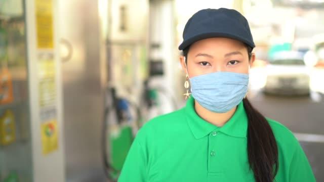 vídeos de stock e filmes b-roll de portrait of female gas station attendant with face mask at work - frentista