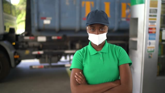 vídeos de stock, filmes e b-roll de retrato de atendente de posto de gasolina com máscara facial no trabalho - braços cruzados