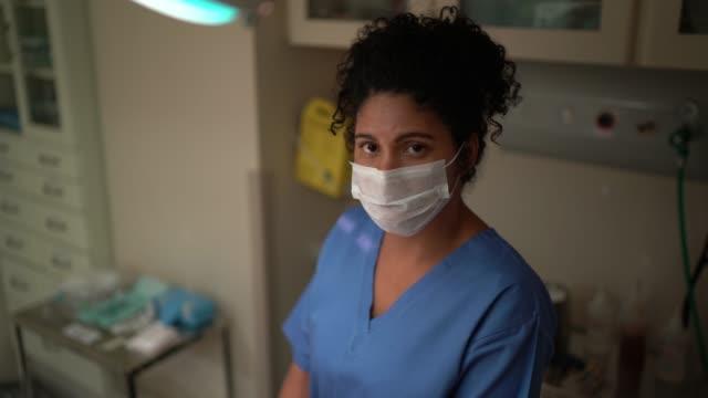 vídeos de stock, filmes e b-roll de retrato de funcionária de saúde com máscara facial na sala de cirurgia do hospital - afro