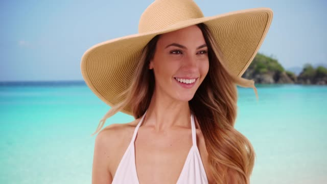 portrait of female in bikini modeling floppy hat on beach in the caribbean - hat stock videos and b-roll footage